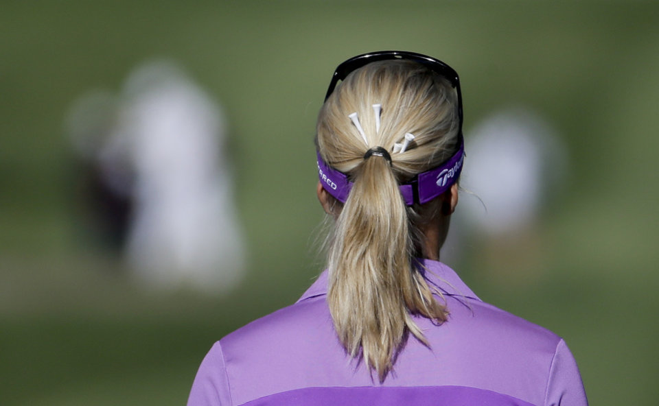 Photo - Anna Nordqvist, of Sweden, with golf tees in her hair, walks down the 15th fairway during the first round at the LPGA Kraft Nabisco Championship golf tournament Thursday, April 3, 2014, in Rancho Mirage, Calif. (AP Photo/Chris Carlson)