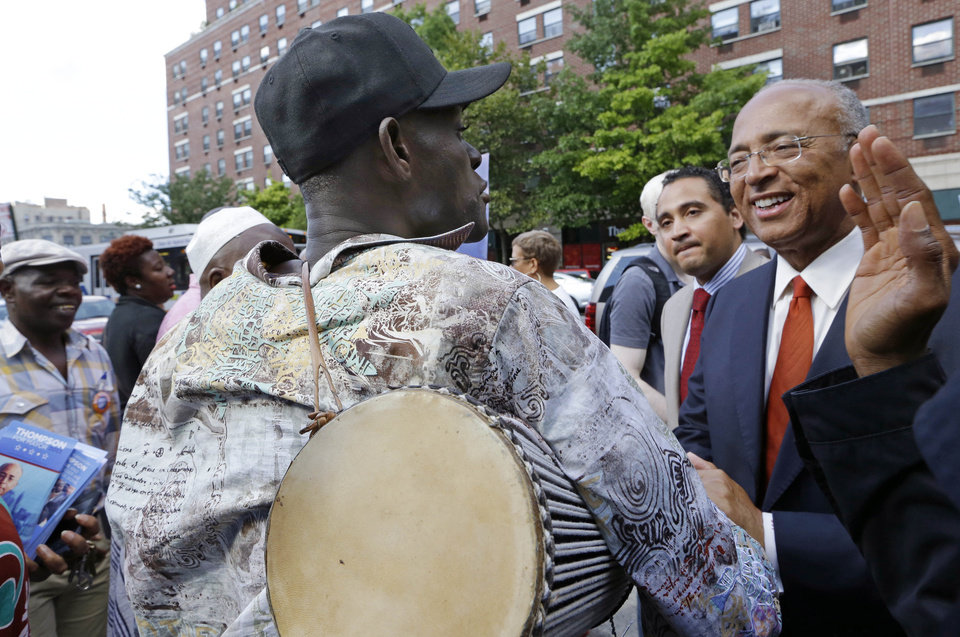 Malian talking drum master Baye Kouyate, left, says farewell to New York City Democratic Mayoral hopeful Bill Thompson after accompanying Thompson on a tour of West-African owned businesses in the Harlem neighborhood of New York, Thursday, Sept. 5, 2013. The Democratic primary election is Tuesday, Sept. 10. (AP Photo/Kathy Willens)