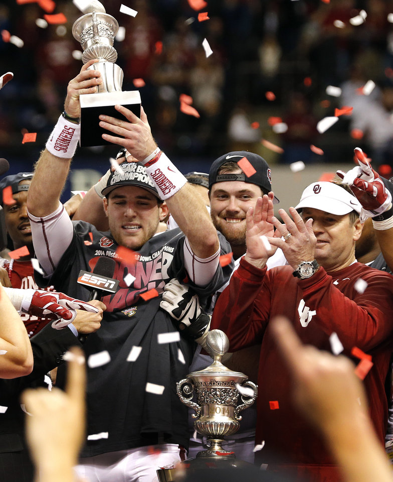 Photo - Oklahoma's Trevor Knight (9) holds up the MVP trophy as the Sooners celebrate the 45-31 win over Alabama during the NCAA football BCS Sugar Bowl game between the University of Oklahoma Sooners (OU) and the University of Alabama Crimson Tide (UA) at the Superdome in New Orleans, La., Thursday, Jan. 2, 2014.  .Photo by Chris Landsberger, The Oklahoman