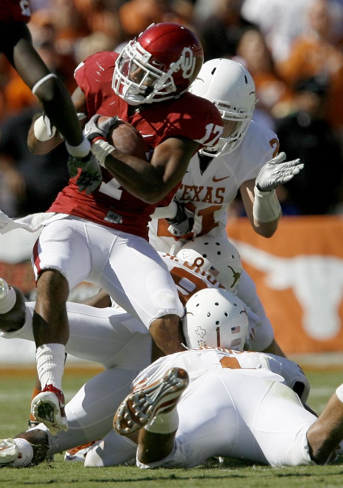 Photo - OU's Mossis Madu is brought down by Blake Gideon, top, Chykie Brown, and Keenan Robinson of Texas during the first half of the Red River Rivalry college football game between the University of Oklahoma Sooners (OU) and the University of Texas Longhorns (UT) at the Cotton Bowl on Saturday, Oct. 2, 2010, in Dallas, Texas.   Photo by Bryan Terry, The Oklahoman