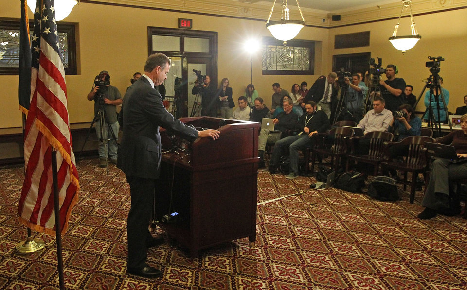 Photo - Utah Attorney General John Swallow looks down during a news conference Thursday, Nov. 21, 2013, in Salt Lake City. Swallow announced that he is stepping down amid multiple investigations of bribery and misconduct that have hounded him ever since he took office at the beginning of the year. (AP Photo/Rick Bowmer)