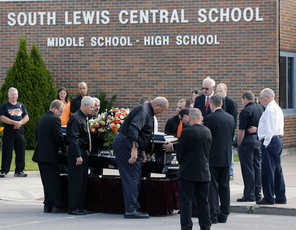 Photo - The casket of race car driver Kevin Ward Jr., is taken from a hearse before being carried into South Lewis Central School before a funeral on Thursday, Aug. 14, 2014, in Turin, N.Y. Ward died after being struck by NASCAR driver Tony Stewart's car during a race last weekend at a dirt track in western New York. (AP Photo/Mike Groll)