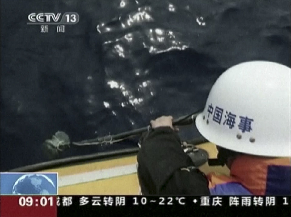 Photo - In this image taken from video, a member of a Chinese search team uses an instrument to detect electronic pulses while searching for the missing Malaysia Airlines Flight 370, on board the patrol vessel Haixun 01, in the search area in the southern Indian Ocean, Saturday, April 5, 2014. China's official Xinhua News Agency reported late Saturday that the patrol vessel Haixun 01 had detected a