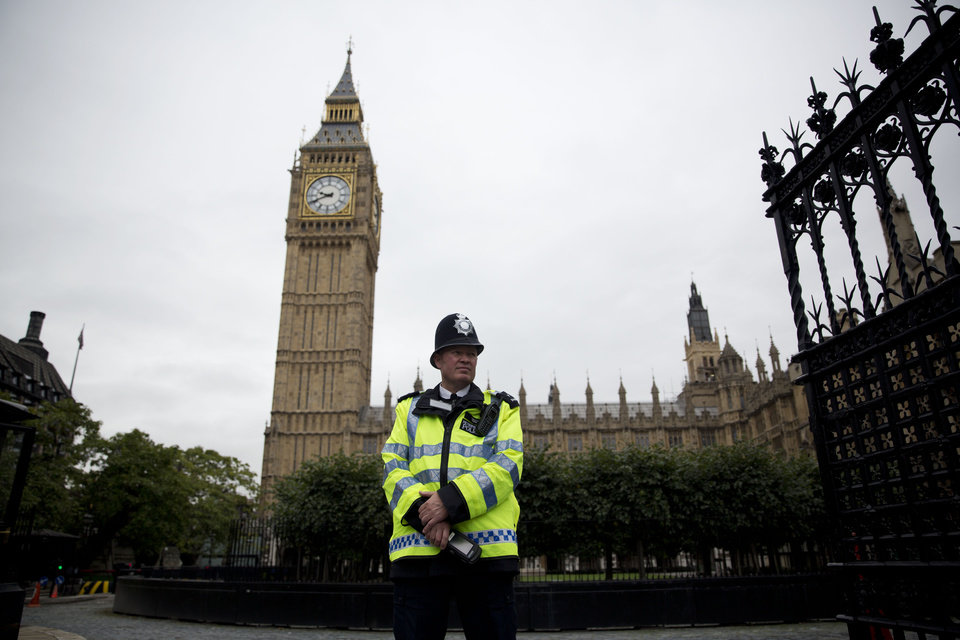 Photo - A British police officer stands guard outside the Houses of Parliament in London, Monday, Sept. 1, 2014.  Britain's Prime Minister David Cameron is expected on Monday to expand powers to combat terrorism in hopes of preventing attacks by Islamist militants returning from terror training in the Middle East.  (AP Photo/Matt Dunham)