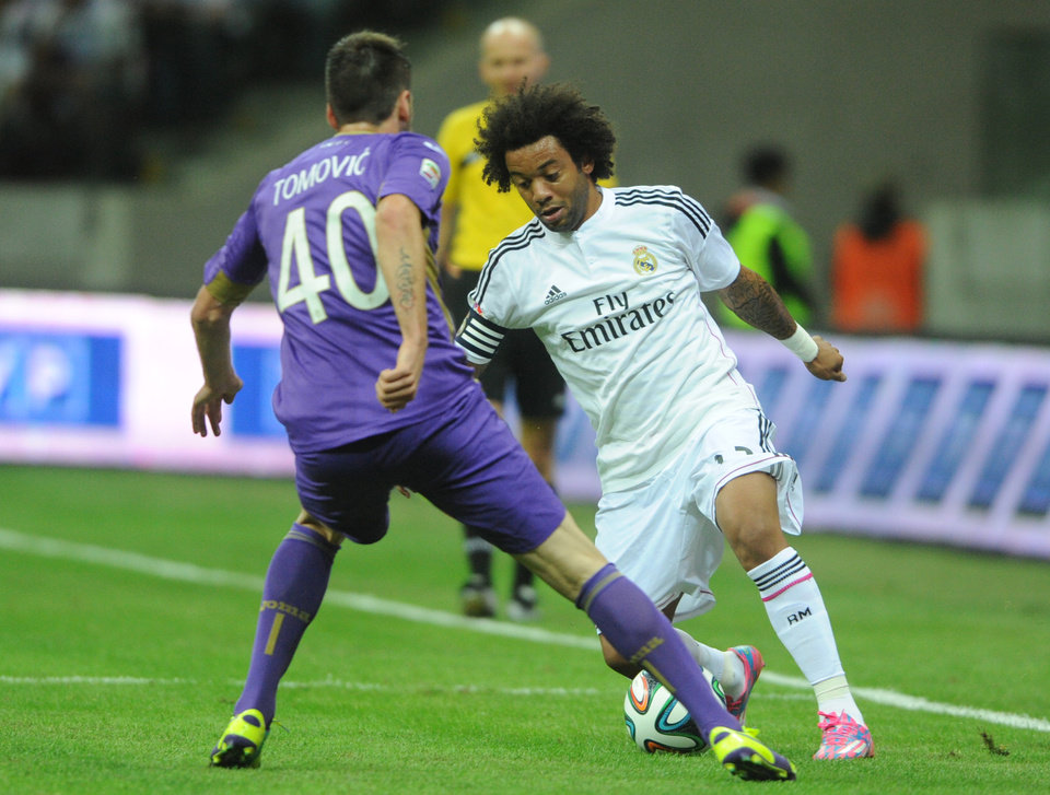 Photo - Real Madrid's Marcelo from Brazil, right, challenge for the ball with Fiorentina's Nenad Tomovic from Serbia during their friendly soccer match in Warsaw, Poland, Saturday, Aug. 16, 2014. ( AP Photo/Alik Keplicz)