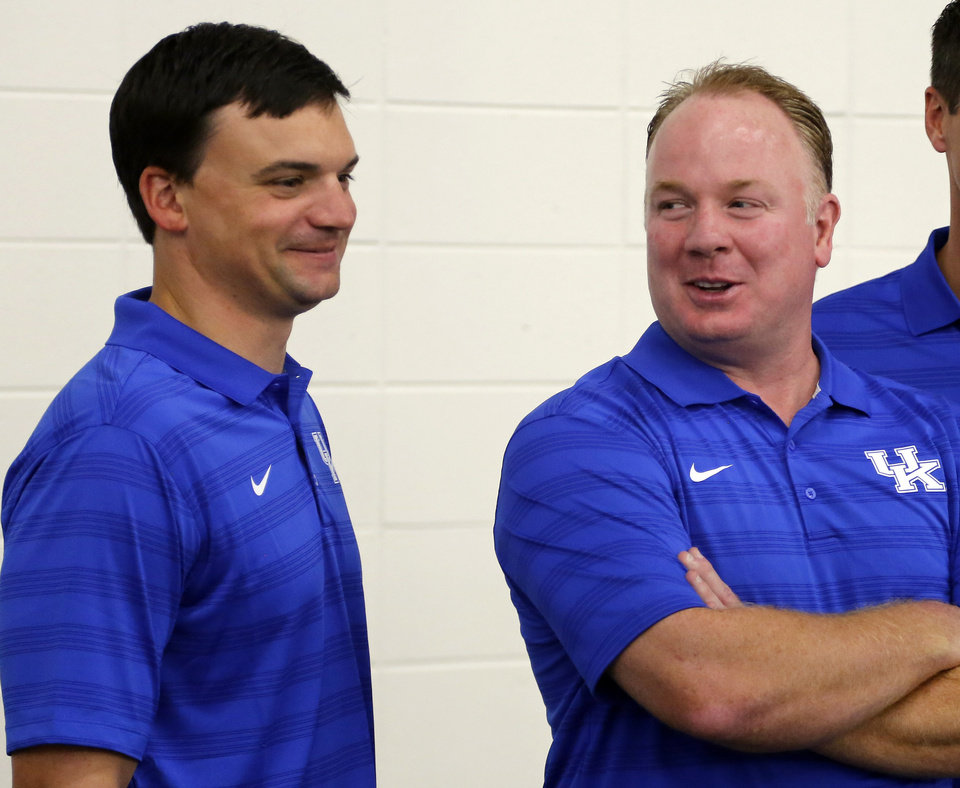 Photo - Kentucky head coach Mark Stoops, right and offensive coordinator Neal Brown share a laugh during the team's NCAA college football media day, Friday, Aug. 8, 2014, in Lexington, Ky. (AP Photo/James Crisp)