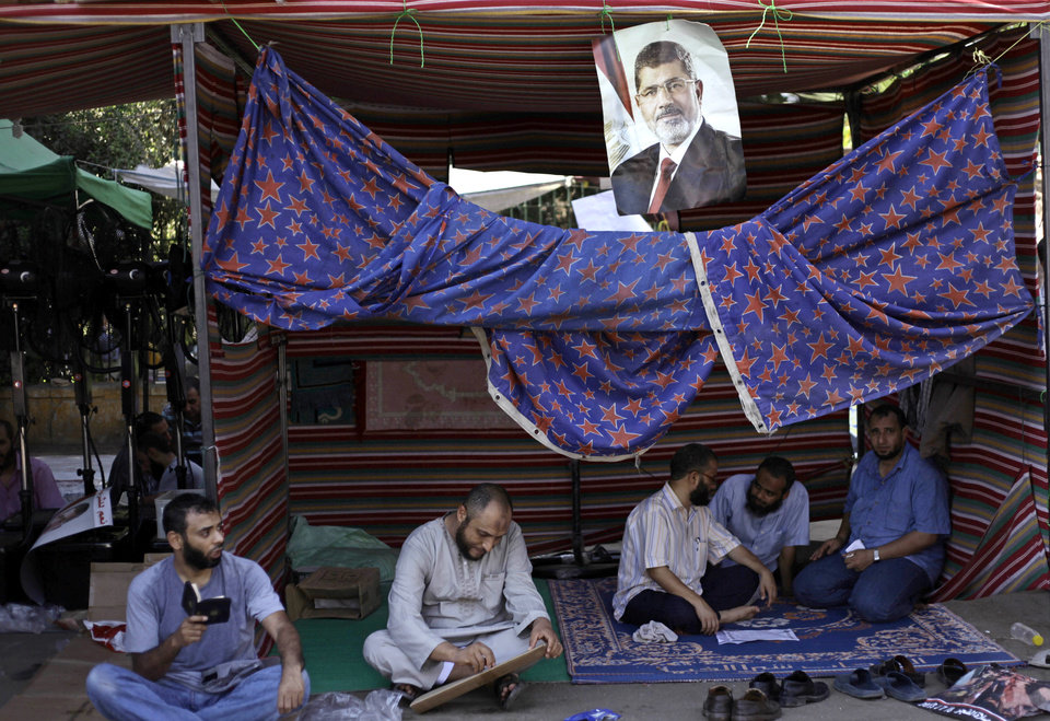 Photo - Supporters of Egypt's ousted President Mohammed Morsi read the Quran during a protest near Cairo University in Giza, Egypt, Friday, July 26, 2013. Egyptian prosecutors accused Morsi on Friday of conspiring with the Palestinian militant group Hamas and murder in his 2011 escape from prison that left 14 guards dead. The development fueled the likelihood of clashes as tens of thousands of supporters and opponents of the Islamist leader massed for rival rallies. A poster with the photo of Morsi is seen top center. (AP Photo/Nariman El-Mofty)