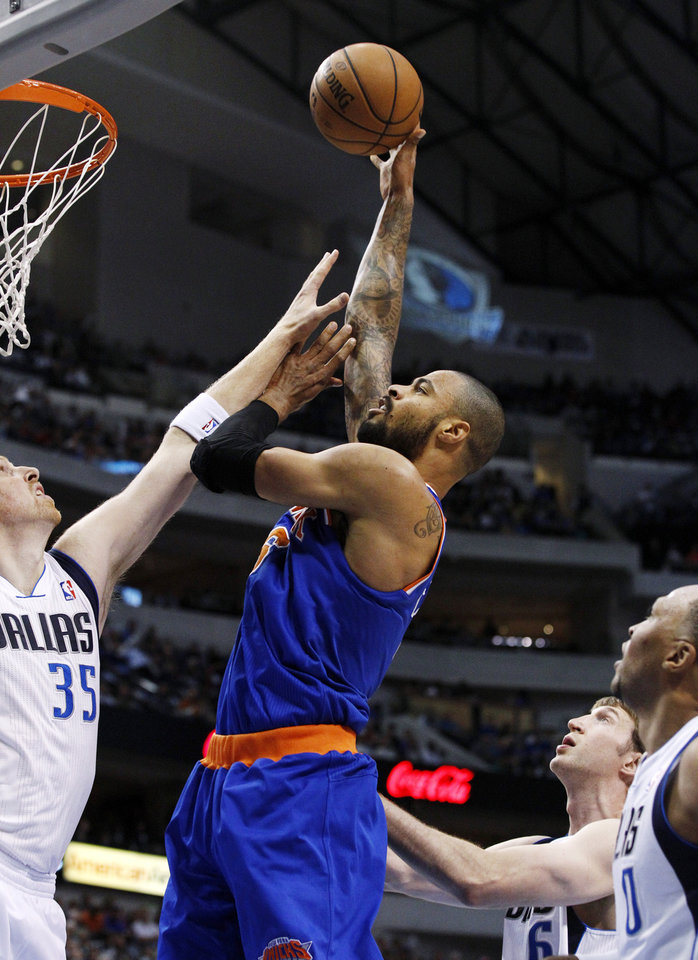 Dallas Mavericks' Chris Kaman (35), Shawn Marion (0) and Troy Murphy, rear, defend as New York Knicks' Tyson Chandler, center, shoots in the first half of an NBA basketball game, Wednesday, Nov. 21, 2012, in Dallas. (AP Photo/Tony Gutierrez)