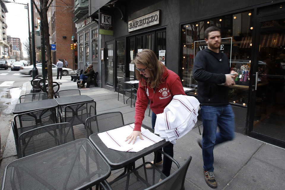 Photo - In this Tuesday, April 1, 2014 photo, workers prepare an outside seating area at Barbuzzo, a Mediterranean kitchen and bar, along 13th Street in Philadelphia. Tourism officials will tell you the restaurant-rich area in the heart of downtown is called Midtown Village, but that moniker hasn't entirely caught on with locals. Philadelphia food lovers just know 13th Street as a vibrant area chock full of great eateries and wine bars. (AP Photo/Matt Slocum)
