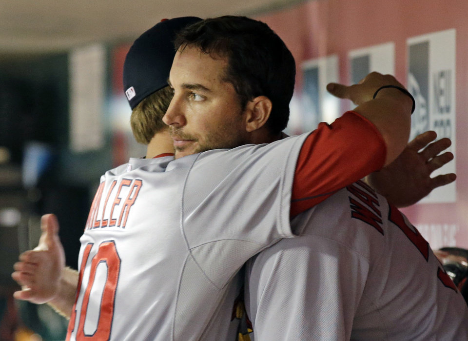 Photo - St. Louis Cardinals starting pitcher Adam Wainwright is hugged by Shelby Miller, left, after Wainwright was taken out at the end of the eighth inning of a baseball game against the Cincinnati Reds, Sunday, May 25, 2014, in Cincinnati. Wainwright earned the win with eighth shutout innings and 12 strikeouts. St. Louis won 4-0. (AP Photo/Al Behrman)
