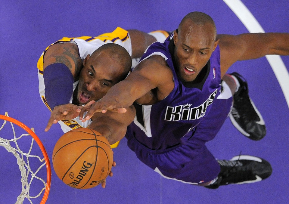 Los Angeles Lakers guard Kobe Bryant, left, and Sacramento Kings forward Travis Outlaw go after a rebound during the first half of their NBA basketball game, Sunday, Nov. 11, 2012, in Los Angeles. (AP Photo/Mark J. Terrill)