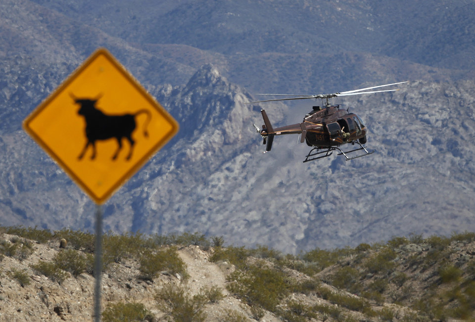 Photo - A helicopter takes off from a staging area of Bureau of Land Management vehicles and other government vehicles off of Riverside Road near Bunkerville, Nev. Saturday, April 5, 2014. the U.S. Bureau of Land Management started taking cattle on Saturday from rancher Cliven Bundy, who it says has been trespassing on U.S. land without required grazing permits for over 25 years. Bundy doesn't recognize federal authority on land he insists belongs to Nevada. (AP Photo/Las Vegas Review-Journal, John Locher)