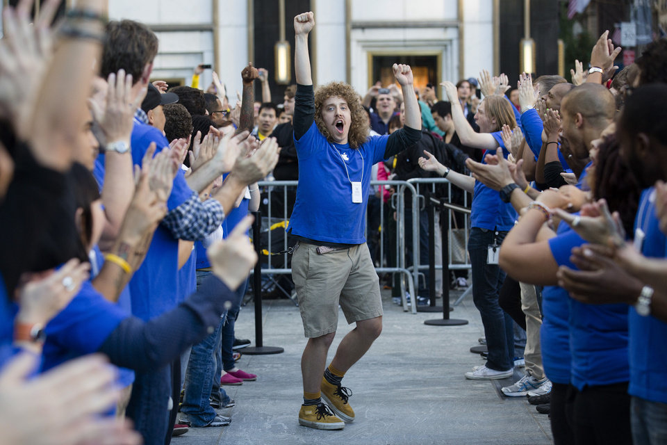 Photo -   An Apple employee riles up his coworkers outside the Fifth Avenue Apple store to celebrate the release of the iPhone 5, Friday, Sept. 21, 2012, in New York. Hundreds of people waited in line through the early morning to be among the first to get their hands on the highly anticipated phone. (AP Photo/John Minchillo)