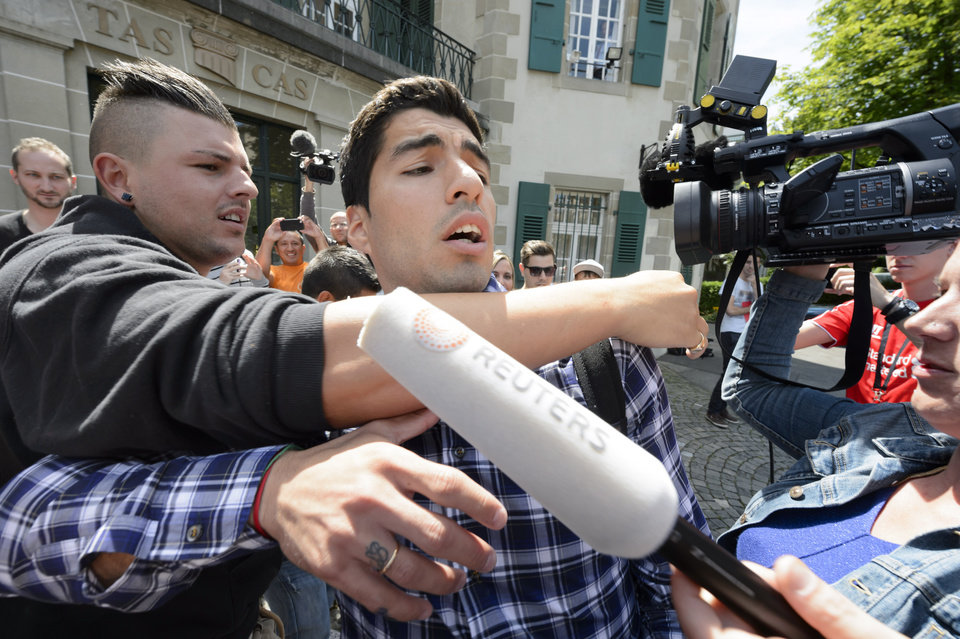Photo - Uruguay's soccer player Luis Suarez leaves the international Court of Arbitration for Sport, CAS, surrounded by fans and media after a five hour hearing in Lausanne, Switzerland, Friday, Aug. 8, 2014. Suarez appealed to the CAS against the four-month ban imposed by FIFA on the Uruguay striker. Suarez was banned for biting Italy's Giorgio Chiellini at the FIFA Brazil 2014 World Cup. (AP Photo/Keystone, Laurent Gillieron)