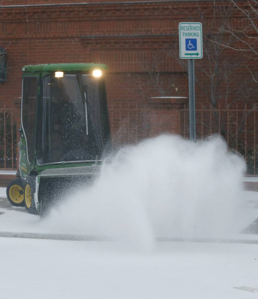 Photo - A city worker clears snow from a sidewalk on Massachusetts Street in Lawrence, Kan., Sunday, March 2, 2014. The area is under a winter storm warning and is expecting more snow throughout the day. (AP Photo/Orlin Wagner)