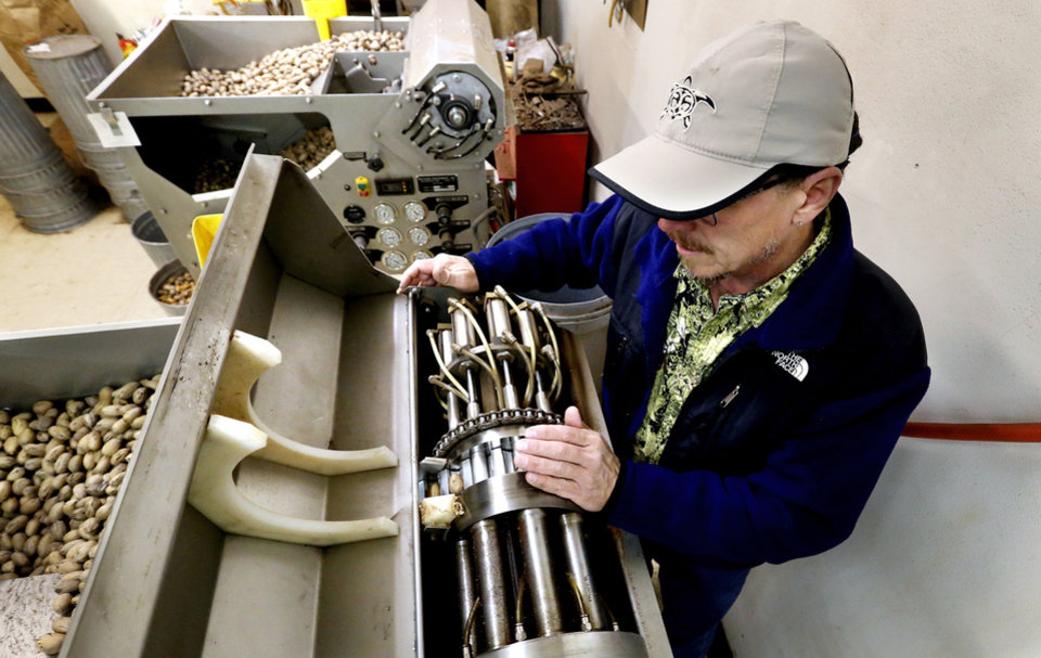 Brett Mason with Mason's Pecans & Peanuts shows the inside of a Savage high-speed cracking machine. PHOTO BY STEVE SISNEY, THE OKLAHOMAN <strong>STEVE SISNEY</strong>