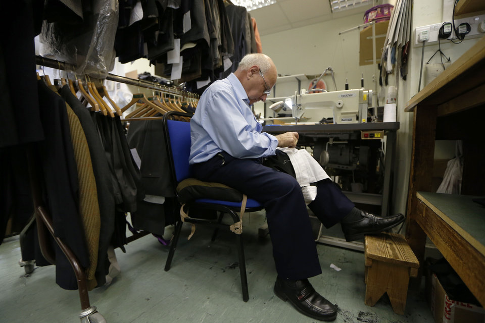 Photo - In this photo taken Friday, June 6, 2014, a tailor works on a suit at Henry Poole & Co tailor, the first shop to set up in Savile Row in 1846, in London. In the world of women's fashion, London often seems to play second fiddle to other style capitals: It lacks the allure of Paris's haute couture, or the polish of Milan's luxury labels. But it's a whole different story when it comes to dressing men. Steeped in a rich history of tailoring for kings, army generals and the world's wealthiest men, London is now marketed as the home of men's fashion - the original birthplace of the tuxedo jacket, the bowler hat and the three-piece suit, among other classic items. When trendy designers like Alexander McQueen and Burberry kick off the new season's menswear shows in the British capital Sunday, the catwalks will be staged just blocks away from elite tailoring houses that have been perfecting their craft for over a century. Savile Row, a street lined with more than a dozen tailors and a living museum of the English love affair with luxury menswear, has a long-standing tradition closely tied to a history in royal dress, military uniforms and gentry sports like horseback riding and hunting. (AP Photo/Sang Tan)