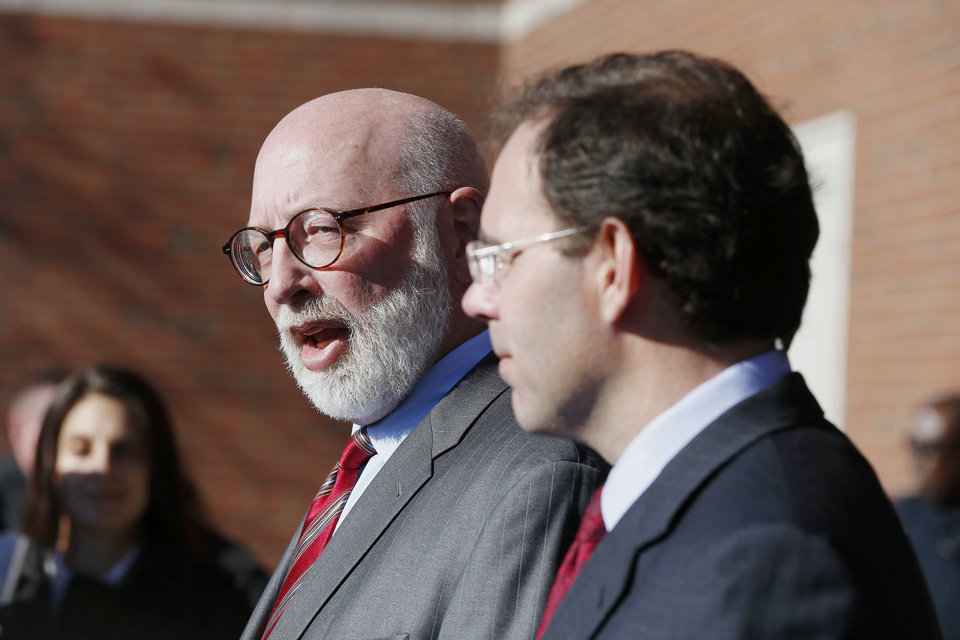 Photo - Defense attorneys J.W. Carney Jr., center, and Henry Brennan, right, speak with reporters after a sentencing hearing for their client James