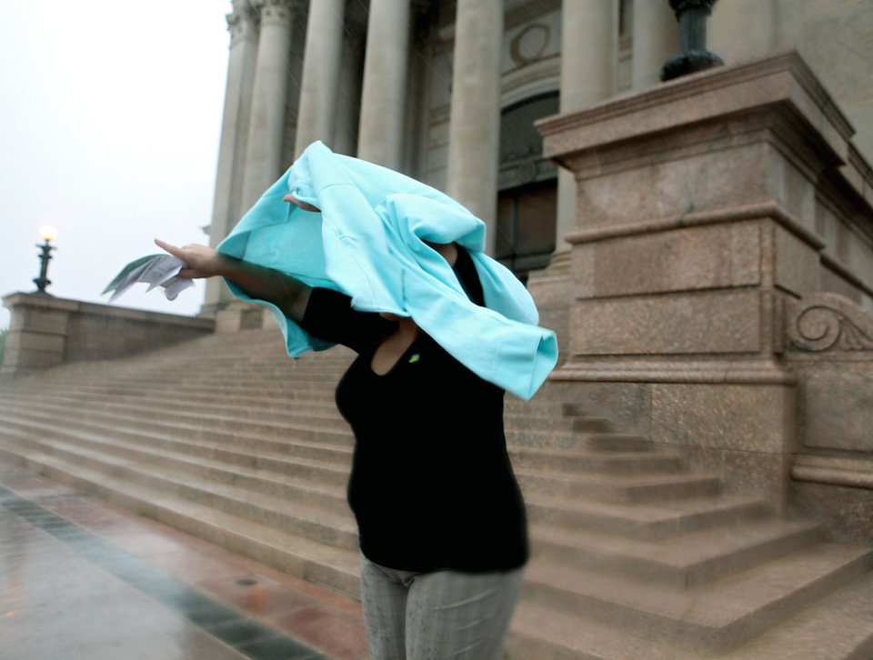 Bobbi Carter, a visitor to the state Capitol in Oklahoma City, tries to keep dry on Wednesday, April 29, 2009. Photo by John Clanton