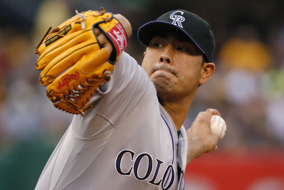 Photo - Colorado Rockies starting pitcher Jorge De La Rosa delivers during the first inning of a baseball game against the Pittsburgh Pirates in Pittsburgh on Friday, July 18, 2014. (AP Photo/Gene J. Puskar)