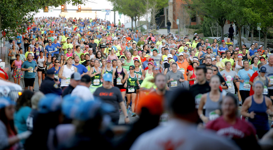 Photo - Runners make their way east on NE 4th Street during the Oklahoma City Memorial Marathon in Oklahoma City, Sunday, April 29, 2018. Photo by Bryan Terry, The Oklahoman