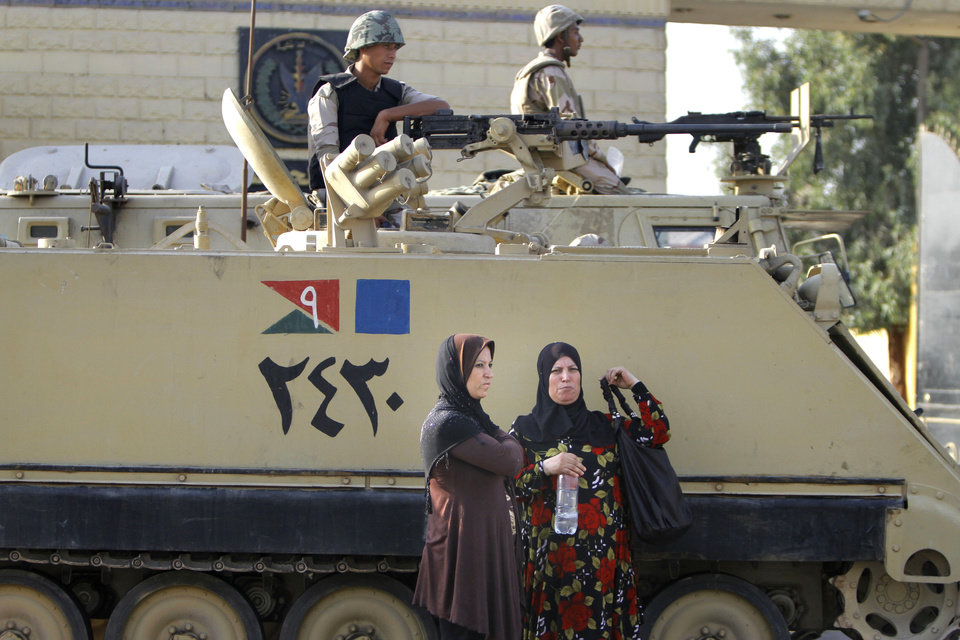 Photo - Egyptian women wait near an armored army vehicle guarding Torah Prison, where ousted President Hosni Mubarak is held in Cairo, Egypt, Wednesday, Aug. 21, 2013. An Egyptian court ordered Wednesday the release of ousted President Hosni Mubarak, but it is not yet clear if the ailing ex-leader will walk free after over two years in detention, officials said. The prospects of Mubarak's release after the 2011 uprising against him, and a slew of court cases that made him the first Arab leader to be tried by his own people, are likely to further fuel the rest that has hit Egypt following the military coup against his successor, the first freely elected president Islamist Mohammed Morsi. (AP Photo/Amr Nabil)