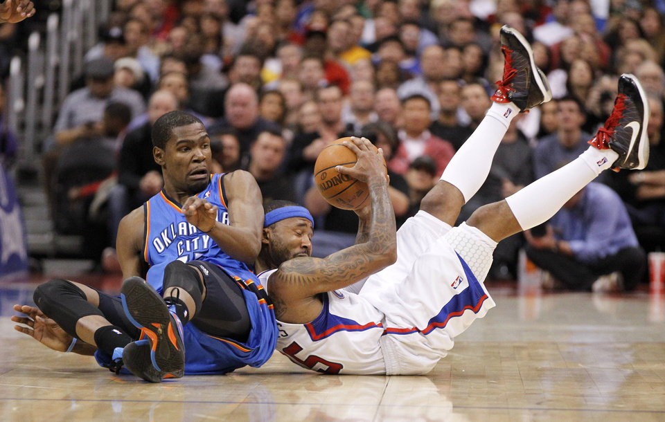 Photo - Oklahoma City Thunder forward Kevin Durant, left, watches Los Angeles Clippers' Mo Williams grab a loose ball during the first half of an NBA basketball game in