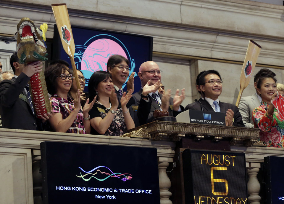 Photo - Stephen Barclay, center, director of the Hong Kong Economic and Trade Office, is joined in applause during New York Stock Exchange opening bell ceremonies, Wednesday, Aug. 6, 2014, to mark the upcoming 24th Annual Hong Kong Dragon Boat Festival. (AP Photo/Richard Drew)