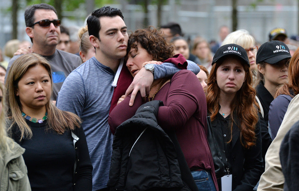 Photo - Two people embrace while gathered on the plaza of the National September 11 Memorial to watch the telecast of the dedication ceremony at the National September 11 Memorial Museum in New York on Thursday, May 15, 2014.  (AP Photo/Justin Lane, Pool)