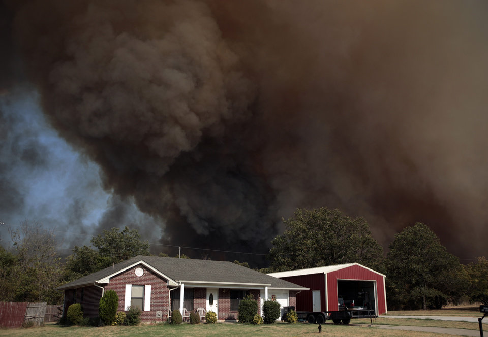 Photo - A smoke surrounds home in Luther, Okla.,  during a large wildfire Friday, Aug. 3, 2012. Photo by Sarah Phipps, The Oklahoman