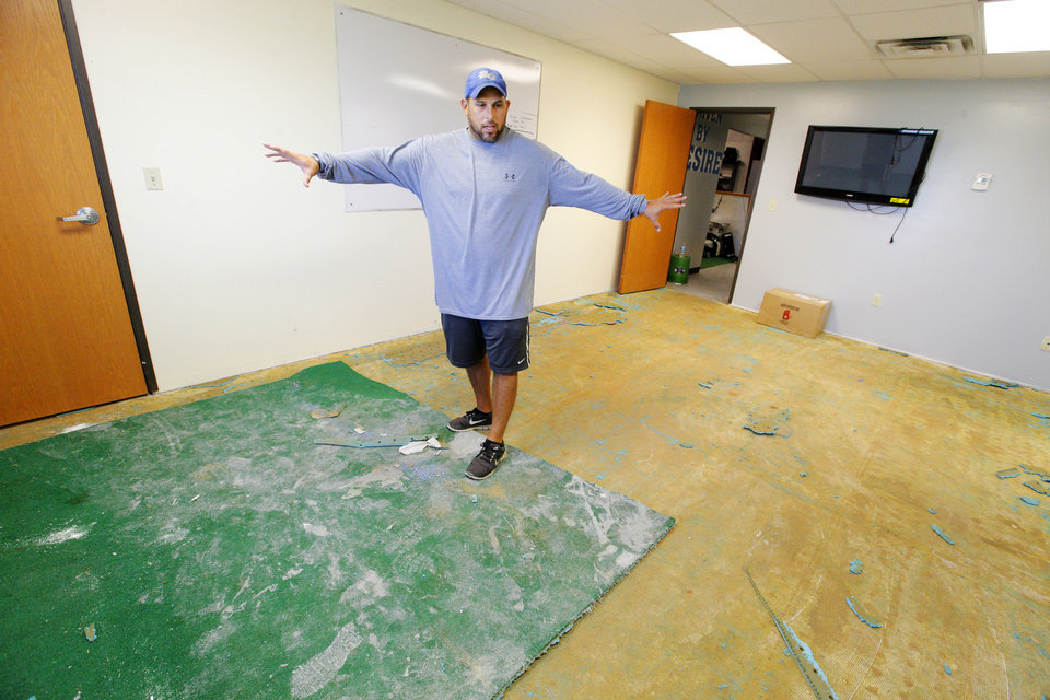 Photo - Coach Greg Wallis surveys the remains of his office in the field house at Bridge Creek High School in Bridge Creek Monday, Aug. 11, 2014.  Vandals spread paint, carpet glue, and rat poison on football equipment and furniture throughout the building. Carpets had to be removed and many items placed in the trash leaving Bridge Creek without enough helmets, jerseys and other equipment .  Photo by Paul B. Southerland, The Oklahoman