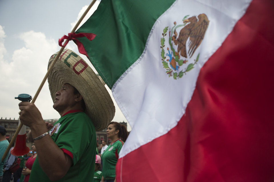 Photo - A Mexico soccer fan holds a flag as he watches his team's World Cup match with Brazil during a live broadcast on giant television screens in Mexico City's main square, the Zocalo, Tuesday, June 17, 2014. (AP Photo/Rebecca Blackwell)