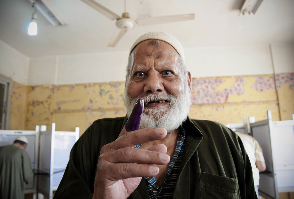 Photo -   An Egyptian man shows his inked finger after casting his vote inside a polling station, in Giza, Egypt, Wednesday, May 23, 2012. More than 15 months after autocratic leader Hosni Mubarak's ouster, Egyptians streamed to polling stations Wednesday to freely choose a president for the first time in generations. (AP Photo/Mohammed Asad)
