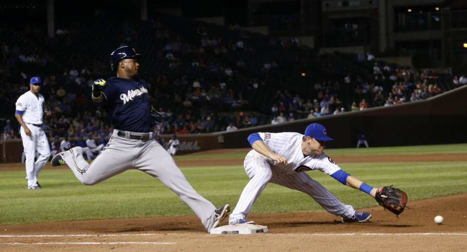 Photo - Milwaukee Brewers' Jean Segura, left, reaches first on a throwing error by Chicago Cubs second baseman Logan Watkins to first baseman Chris Valaika during the ninth inning of a baseball game Wednesday, Sept. 3, 2014, in Chicago. The Cubs won 6-2. (AP Photo/Charles Rex Arbogast)