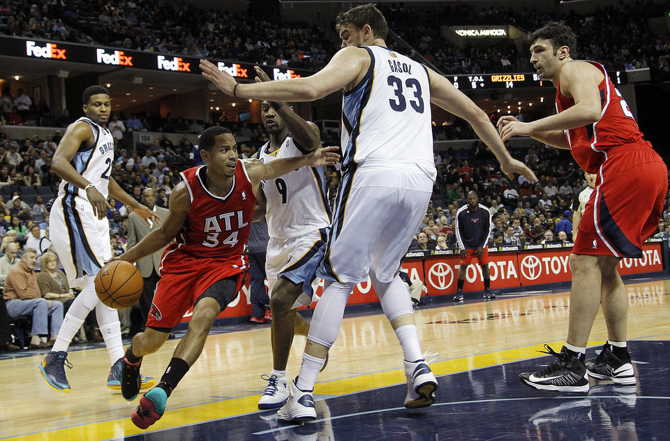 Photo - Atlanta Hawks guard Devin Harris (34) drives to the basket against Memphis Grizzlies defenders Rudy Gay (22), Tony Allen (9) and Marc Gasol (33) with Hawks teammate Zaza Pachulia, right, in the first half of an NBA basketball game on Saturday, Dec. 8, 2012, in Memphis, Tenn. (AP Photo/Lance Murphey)