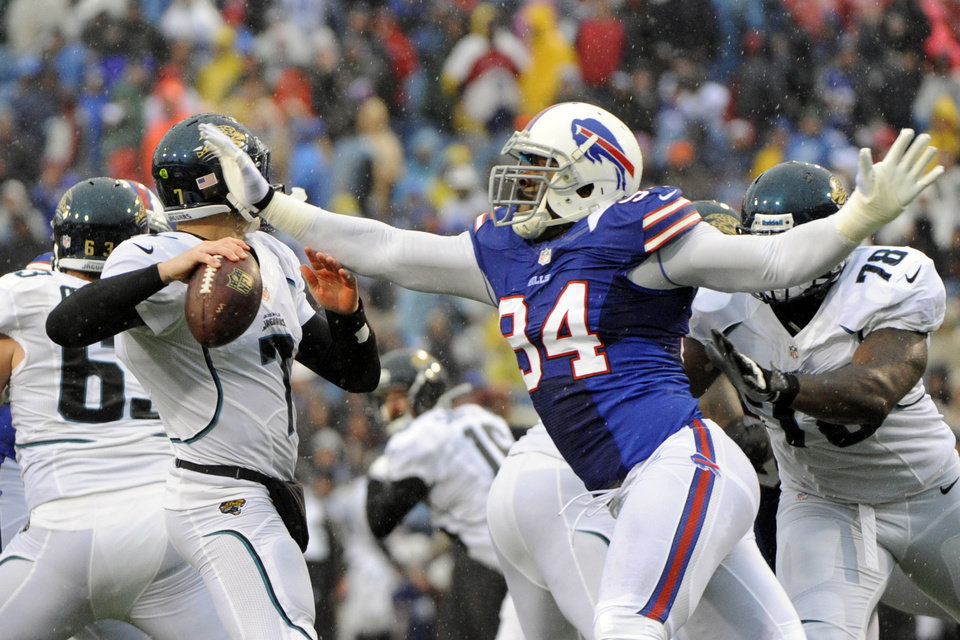 Buffalo Bills defensive end Mario Williams (94) knocks the ball away from Jacksonville Jaguars' Chad Henne (7) during the first half of an NFL football game on Sunday, Dec. 2, 2012, in Orchard Park, N.Y. Williams recovered the fumble on the play. (AP Photo/Gary Wiepert)
