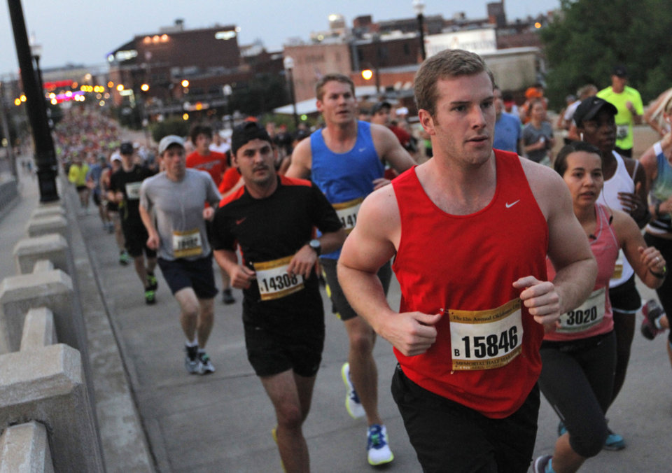 Jordan Rodich (red), of Tulsa, runs across the Walnut Bridge during the twelfth annual Oklahoma City Memorial Marathon in Oklahoma City, Sunday, April 29, 2012. Photo by Garett Fisbeck, For The Oklahoman