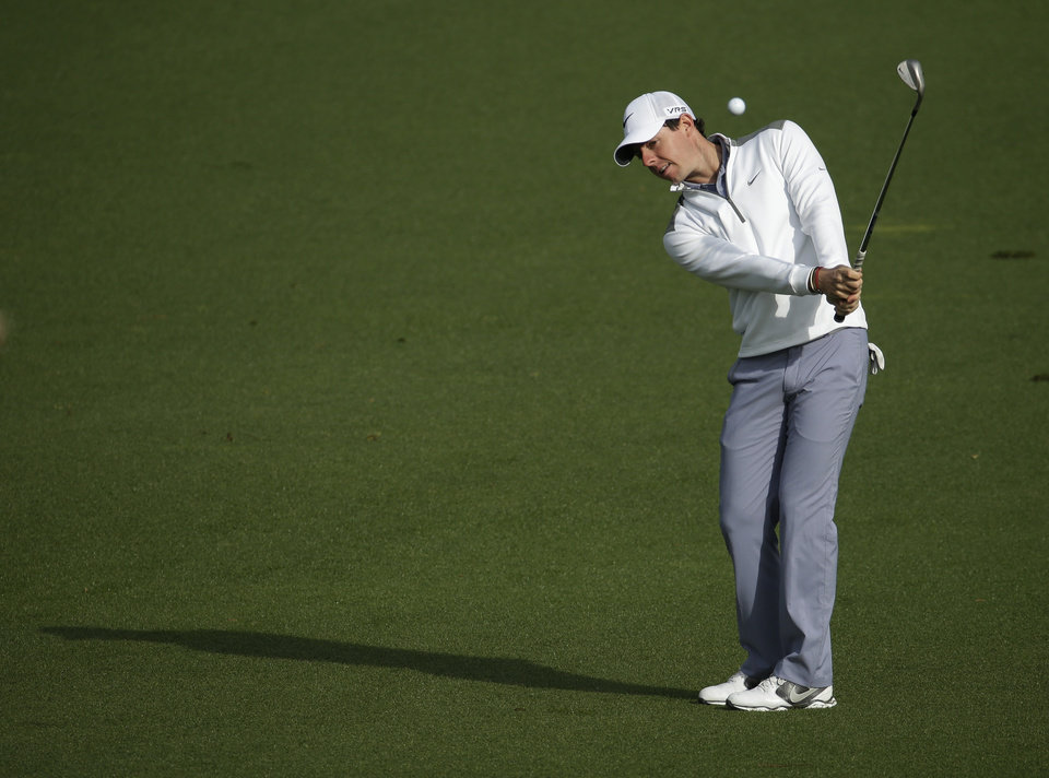 Photo - Rory McIlroy, of Northern Ireland, hits to the second green during a practice round for the Masters golf tournament Tuesday, April 8, 2014, in Augusta, Ga. (AP Photo/Charlie Riedel)