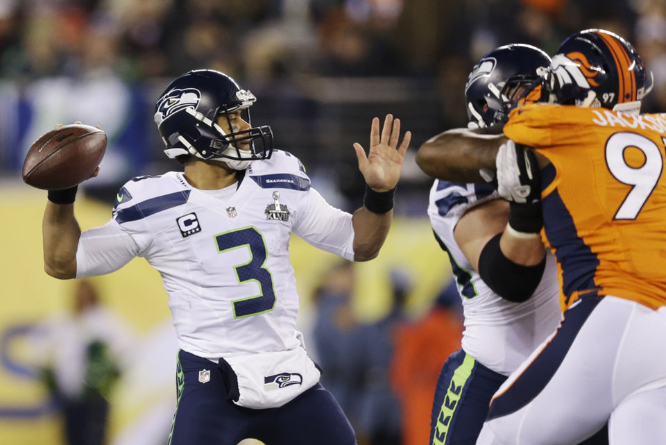 Photo - Seattle Seahawks' Russell Wilson (3) throws against the Denver Broncos during the first half of the NFL Super Bowl XLVIII football game Sunday, Feb. 2, 2014, in East Rutherford, N.J. (AP Photo/Julio Cortez)