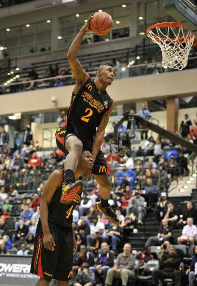 Photo - Oklahoma State signee LeBryan Nash dunks over Adonis Thomas as he competes in the slam dunk contest at the McDonald's High School All American basketball Jam Fest at Chicago State University in Chicago, Monday, March 28, 2011. Nash won. (AP Photo/Brian Kersey)