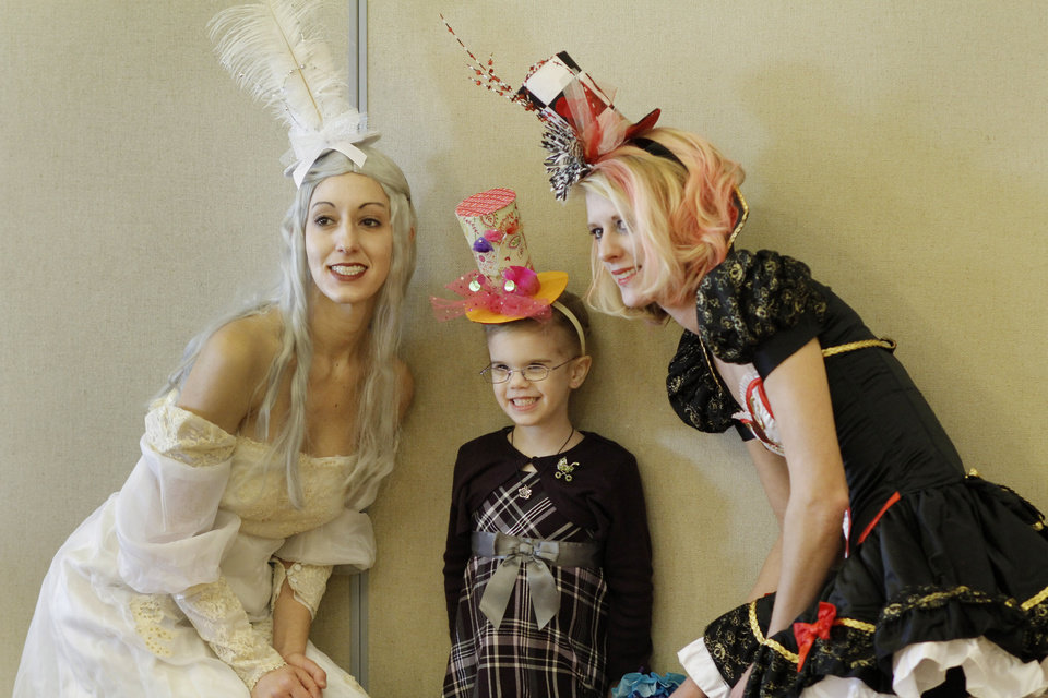 Photo - Isabella Baxter, 5, poses with the queens Melissa Meyers, left, and Sarah White at the Daddy-Daughter Mad Hatter Tea Party at the Edmond Multi-purpose Community Center Sunday, Feb. 12, 2012.  Photo by Doug Hoke, The Oklahoman ORG XMIT: OKC1202091803570754