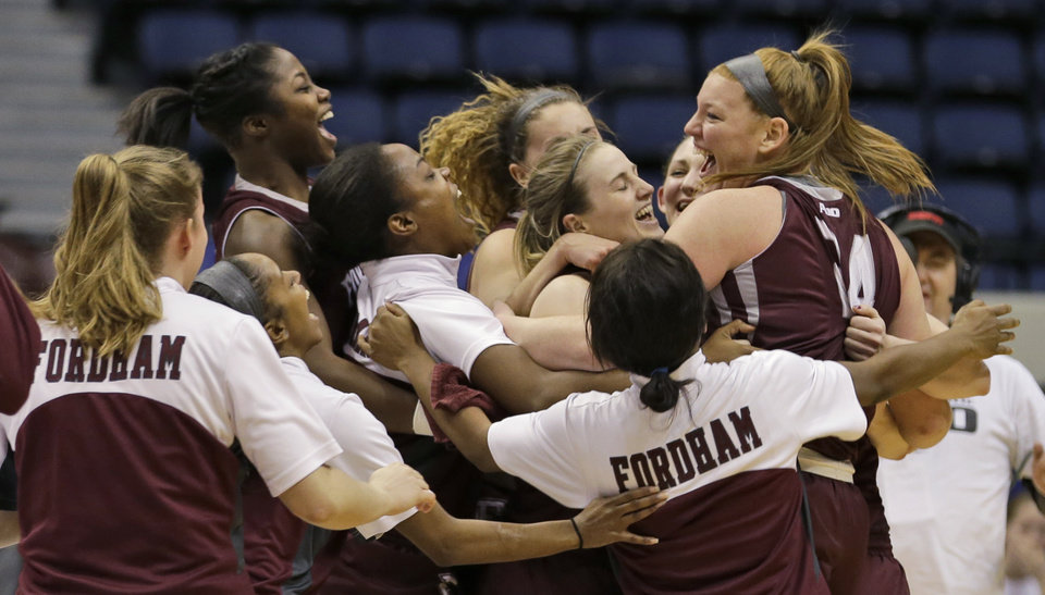 Photo - Members of the Fordham women's basketball team celebrate after winning during the  the A10 Women's basketball championship game against Dayton in Richmond, Va., Sunday, March 9, 2014. Fordham defeated Dayton 63-51. (AP Photo/Steve Helber)