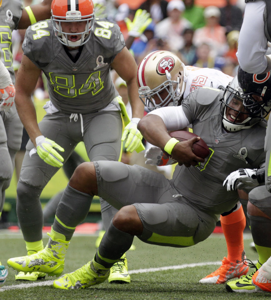 Photo - Carolina Panthers quarterback Cam Newton (1), of Team Sanders, pushes his way in for a touchdown in the second quarter quarter of the NFL Pro Bowl football game as Cleveland Browns tight end Jordan Cameron (84), of Team Sanders, looks on, Sunday, Jan. 26, 2014, in Honolulu. (AP Photo/Eugene Tanner)