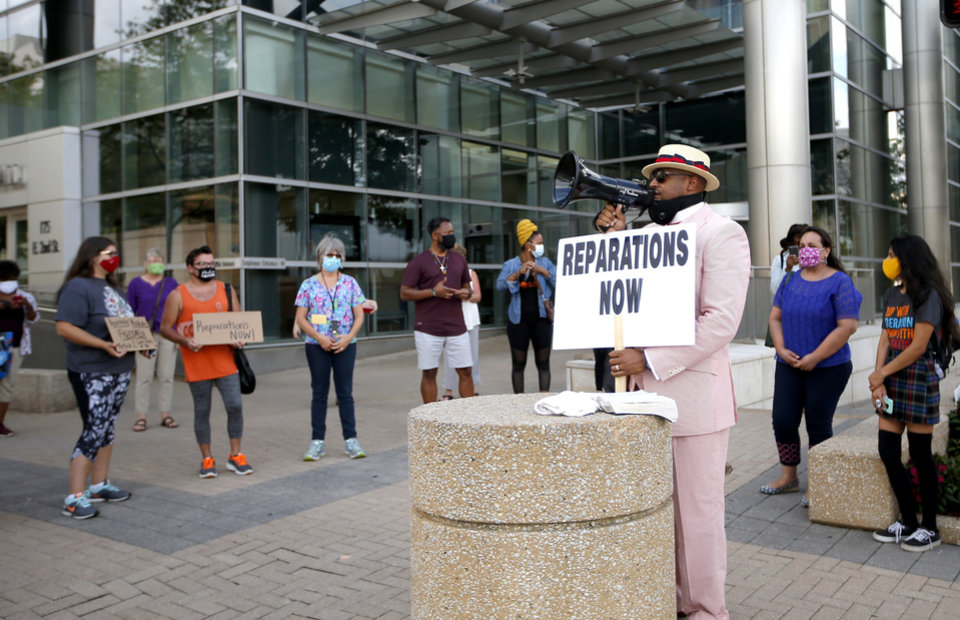 Photo -  The Rev. Robert Turner, senior pastor of Vernon African Methodist Episcopal Church, calls for Tulsa Race Massacre reparations on Wednesday outside Tulsa City Hall. [Sarah Phipps/The Oklahoman]