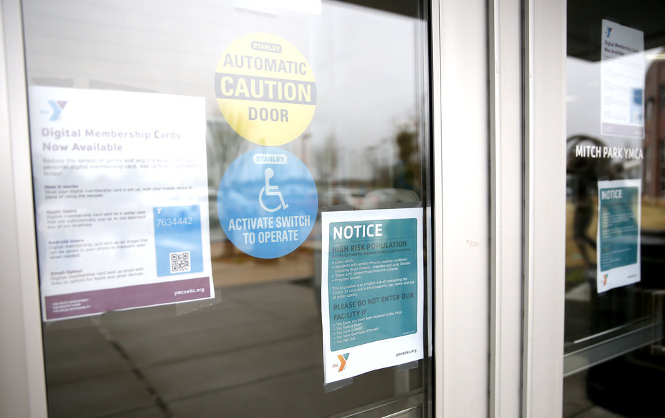 Photo - Signs are pictured on the doors of the Mitch Park YMCA in Edmond, Okla.,  Tuesday, March 17, 2020. [Sarah Phipps/The Oklahoman]