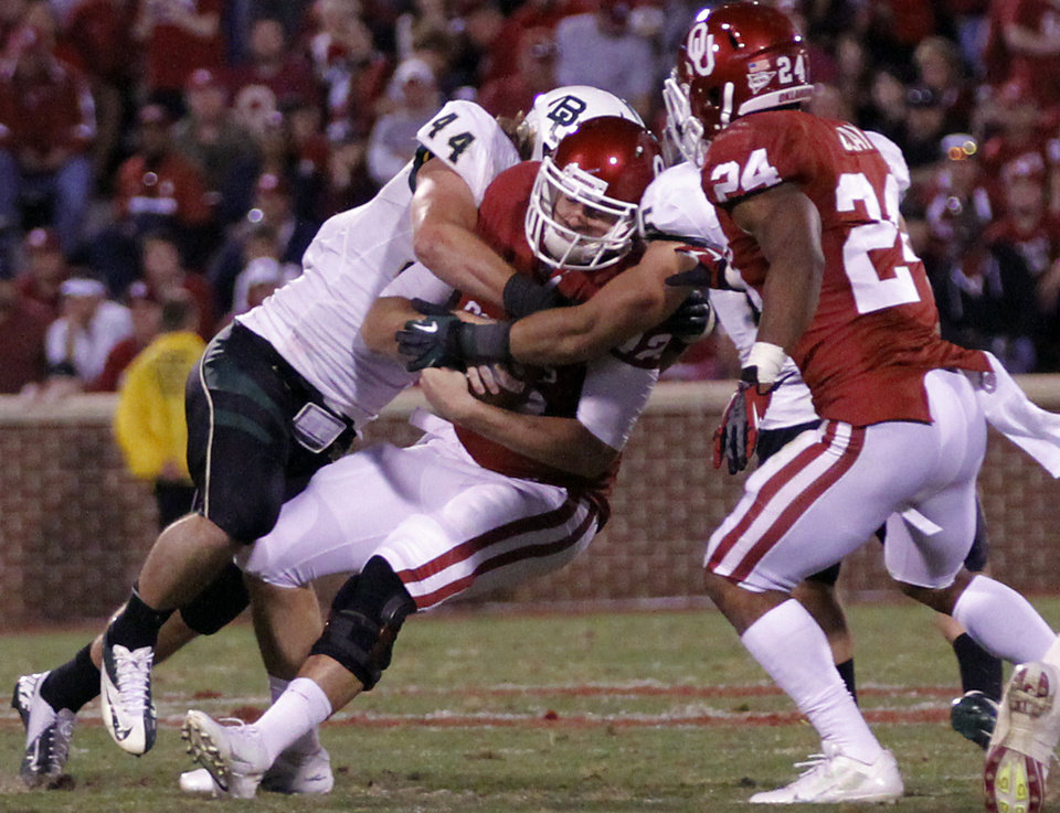 Photo - Baylor's Anthony Webb (14) sacks Oklahoma's Landry Jones (12) during the college football game between the University of Oklahoma Sooners (OU) and Baylor University Bears (BU) at Gaylord Family - Oklahoma Memorial Stadium on Saturday, Nov. 10, 2012, in Norman, Okla.  Photo by Chris Landsberger, The Oklahoman