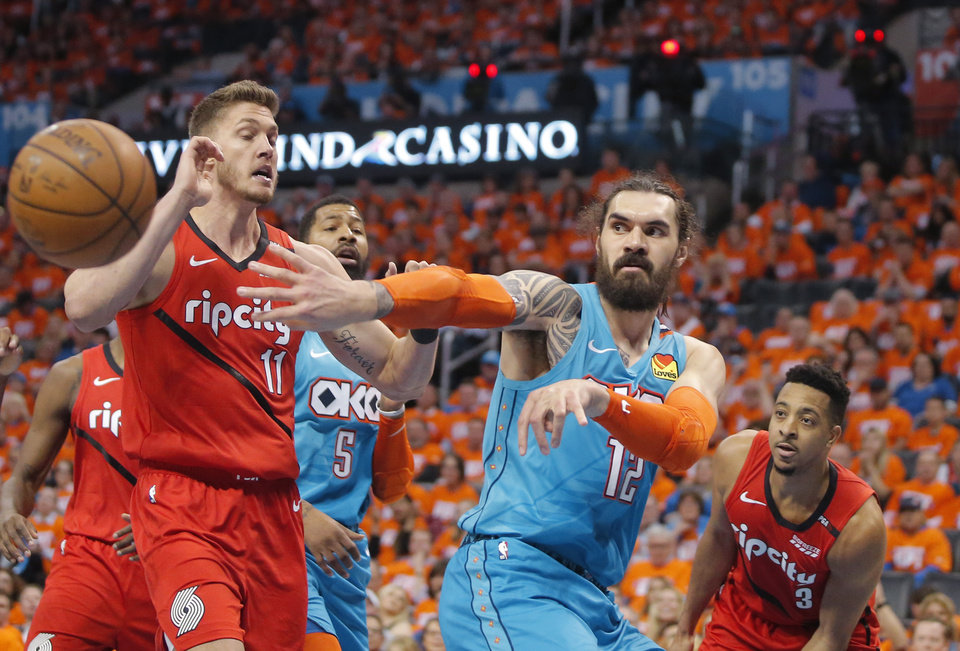 Photo - Oklahoma City's Steven Adams (12) passes the ball from between Portland's Meyers Leonard (11) and CJ McCollum (3) during Game 3 in the first round of the NBA playoffs between the Portland Trail Blazers and the Oklahoma City Thunder at Chesapeake Energy Arena in Oklahoma City, Friday, April 19, 2019. Photo by Bryan Terry, The Oklahoman