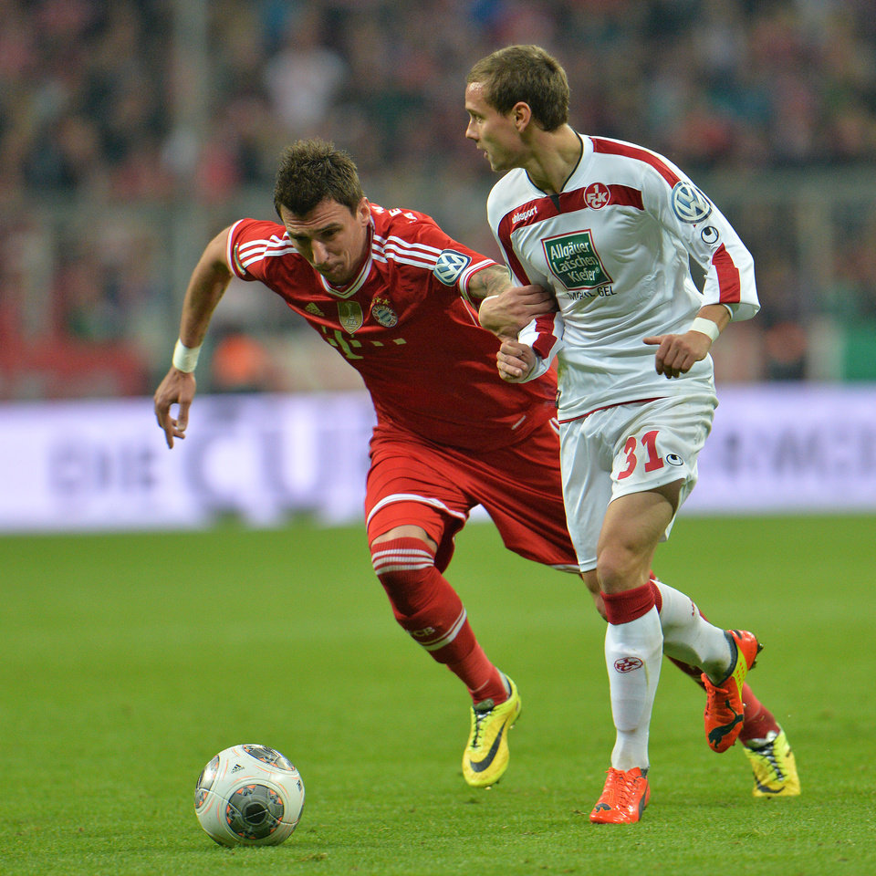 Photo - Munich's Mario Mandzukic of Croatia, left, and Kaiserslautern's Chris Loewe challenge for the ball during the German soccer cup (DFB Pokal) semifinal  match between FC Bayern Munich and FC Kaiserslautern in the Allianz Arena in Munich, Germany, on Wednesday, April 16. 2014. (AP Photo/Kerstin Joensson)