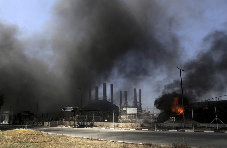 Photo - Smoke and flames rise from the Gaza power plant after it was hit by Israeli strikes, in the Nusseirat Refugee Camp, central Gaza Strip, Tuesday, July 29, 2014. Israel escalated its military campaign against Hamas on Tuesday, striking symbols of the group's control in Gaza and firing tank shells that shut down the strip's only power plant in the heaviest bombardment in the fighting so far. The plant's shutdown was bound to lead to further serious disruptions of the flow of electricity and water to Gaza's 1.7 million people. (AP Photo/Adel Hana)