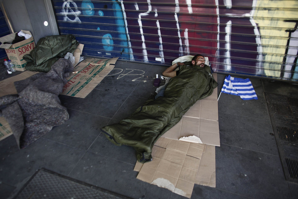 Photo -   A homeless man sleeps on a sidewalk beside a small Greek flag, carried from a party political rally, by his side, in Athens, Saturday May 5, 2012. Greece goes to early polls Sunday while in the throes of a deep financial crisis. No single party is expected to win an overall majority in the 300-member Greek parliament. (AP Photo/Kostas Tsironis)